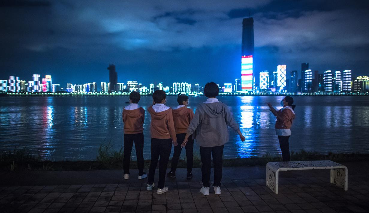 Para anggota tim medis Beijing menikmati panorama sungai di sebuah lokasi di Taman Jiangtan Hankou di Wuhan, Provinsi Hubei, China tengah, pada 26 Maret 2020. Seiring meredanya wabah virus corona (Covid-19), kehidupan di Wuhan berangsur-angsur kembali normal. (Xinhua/Xiao Yijiu)