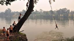 Seorang bocah lelaki melompat ke sungai Penrith saat gelombang panas di Sydney, Kamis (19/12/2019). Pekan ini Australia mengalami rekor hari terpanasnya yang tercatat dalam sejarah dan gelombang panas diperkirakan akan terus meningkat. (Farooq KHAN/AFP)