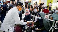 Menteri Perhubungan Budi Karya Sumadi membagikan masker dan penutup wajah kepada para penumpang kereta api hingga pemain musik yang ada di lantai 2 stasiun. (Dok: kemenhub)
