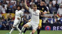 Pemain Real Madrid, Toni Kroos berduel dengan penyerang Atletico Madrid, Fernando Torres (AFP/Gerard Julien)