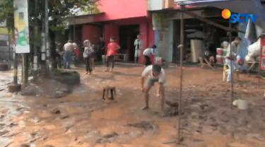 Sebuah alat berat dikerahkan untuk membantu petugas kebersihan dan warga menyingkirkan lumpur hingga arus lalu lintas tersendat.