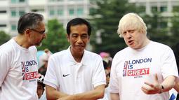 Presiden Joko Widodo (tengah) menyimak pernyataan Walikota London, Boris Johnson (kanan) jelang bersepeda bersama di kawasan Bundaran HI Jakarta, Minggu (30/11/2014). (Liputan6.com/Faizal Fanani)