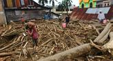 Orang-orang berjalan di atas puing-puing di daerah yang terkena banjir bandang di Masamba, Sulawesi Selatan, Rabu (15/7/2020). Banjir bandang akibat tingginya curah hujan tersebut mengakibatkan 16 orang meninggal dunia dan puluhan warga dilaporkan masih dalam pencarian. (AP/Khaizuran Muchtamir)