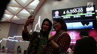 Pekerja berswafoto dengan latar belakan papan pergerakan IHSG usai penutupan perdagangan pasar modal 2017 di BEI, Jakarta, Jumat (29/12). Perdagangan bursa saham 2017 ditutup pada level 6.355,65 poin. (Liputan6.com/Angga Yuniar)