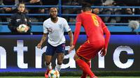 Aksi Raheem Sterling mencoba melewati pemain Montenegro pada laga kedua Kualifikasi Piala Eropa 2020 yang berlangsung di Stadion Pod Goricom, Podgrica, Selasa (26/3). Timnas Inggris menang 5-1 atas Montenegro. (AFP/Andrej Isakovic)
