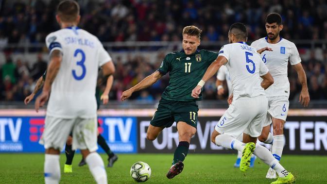 Striker Italia, Ciro Immobile, berusaha melewati bek Yunani, Dimitris Siovas, pada laga Kualifikasi Piala Eropa 2020 di Stadion Olimpico, Roma, Sabtu (12/10). Italia menang 2-1 atas Yunani. (AFP/Alberto Pizzoli)