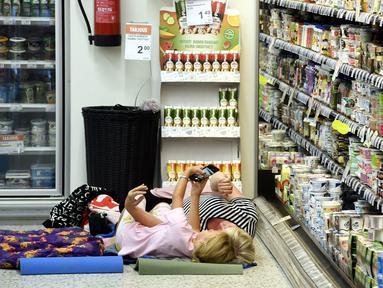 Para wanita berswafoto sambil tidur di atas kasur dekat rak pendingin di sebuah toko kelontong saat gelombang panas melanda Helsinki, Finlandia, 4 Agustus 2018. Para pelanggan mendatangi toko ber-AC ini untuk menginap. (Heikki Saukkomaa/Lehtikuva /AFP)