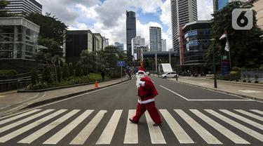 Pria berkostum Sinterklas menyeberang jalan saat membagikan kopi gratis kepada warga di kawasan Jalan Jenderal Sudirman, Jakarta, Sabtu (19/12/2020). Pembagian kopi tersebut bertujuan untuk menyambut perayaan Natal 2020. (Liputan6.com/Johan Tallo)