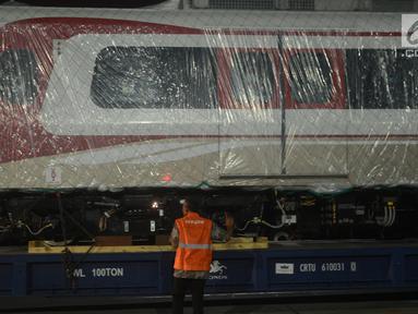 Pekerja mengecek gerbong kereta ringan/Light Rail Transit (LRT) yang baru tiba di Pelabuhan Car Terminal, Tanjung Priok, Jakarta, Jumat (13/4).  Dua gerbong kereta LRT yang diangkut itu merupakan yang pertama tiba di Jakarta. (Merdeka.com/Imam Buhori)