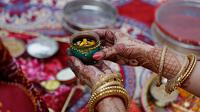 Seorang wanita Hindu yang sudah menikah melakukan ritual festival Karva Chauth di Ahmadabad,  Kamis (17/10/2019). Selama festival Karva Chauth, wanita-wanita yang sudah menikah di India berpuasa sepanjang hari dan memohon umur panjang serta keselamatan untuk suami mereka. (AP/Ajit Solanki)