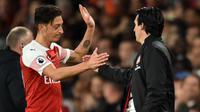 Mesut Ozil bersama Unai Emery. (AFP/Glyn Kirk)