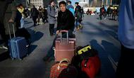 Seorang pria menunggu jadwal keberangkatan kereta di luar stasiun kereta api Beijing di ibu kota China, Senin (21/1). Sebagian warga China yang tinggal di kota-kota besar mulai mudik untuk merayakan tahun baru Imlek bersama keluarga. (WANG ZHAO/AFP)