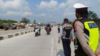 Polisi dan aparat Pemko Pekanbaru memantau perbatasan karena sedang diberlakukan PPKM level 4. (Liputan6.com/M Syukur)