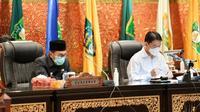 Gubernur Riau Syamsuar (kiri) sebelum terkonfirmasi Covid-19 saat mengikuti sidang paripurna di DPRD. (Liputan6.com/M Syukur)