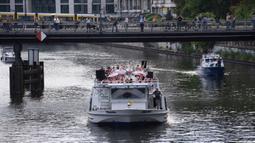Anggota Staatsballett Berlin menari di atas kapal pesiar selama tur melalui pusat kota di Berlin, Jerman, Kamis (10/6/2021). Pertunjukan itu diikuti oleh banyak orang di sepanjang rute. (Paul Zinken/dpa via AP)