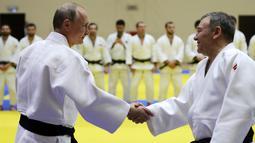 Presiden Rusia, Vladimir Putin menyapa pelatih sebelum mengikuti latihan judo bersama atlet nasional Rusia di Sochi, Kamis (14/2). Judo merupakan salah satu olahraga kegemaran Putin yang telah digeluti sejak masa muda. (Mikhail KLIMENTYEV/SPUTNIK/AFP)