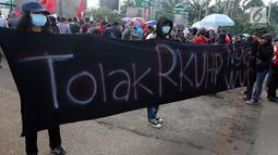 Massa membentangkan spanduk saat melakukan demontrasi di depan Gedung MPR/DPR, Jakarta, Senin (12/2). Mereka menolak KUHP dengan alasan KUHP tidak berpihak pada kelompok marjinal utamanya, Perempuan, Anak, ODHA, Minoritas, LGBT. (Liputan6.com/Johan Tallo)