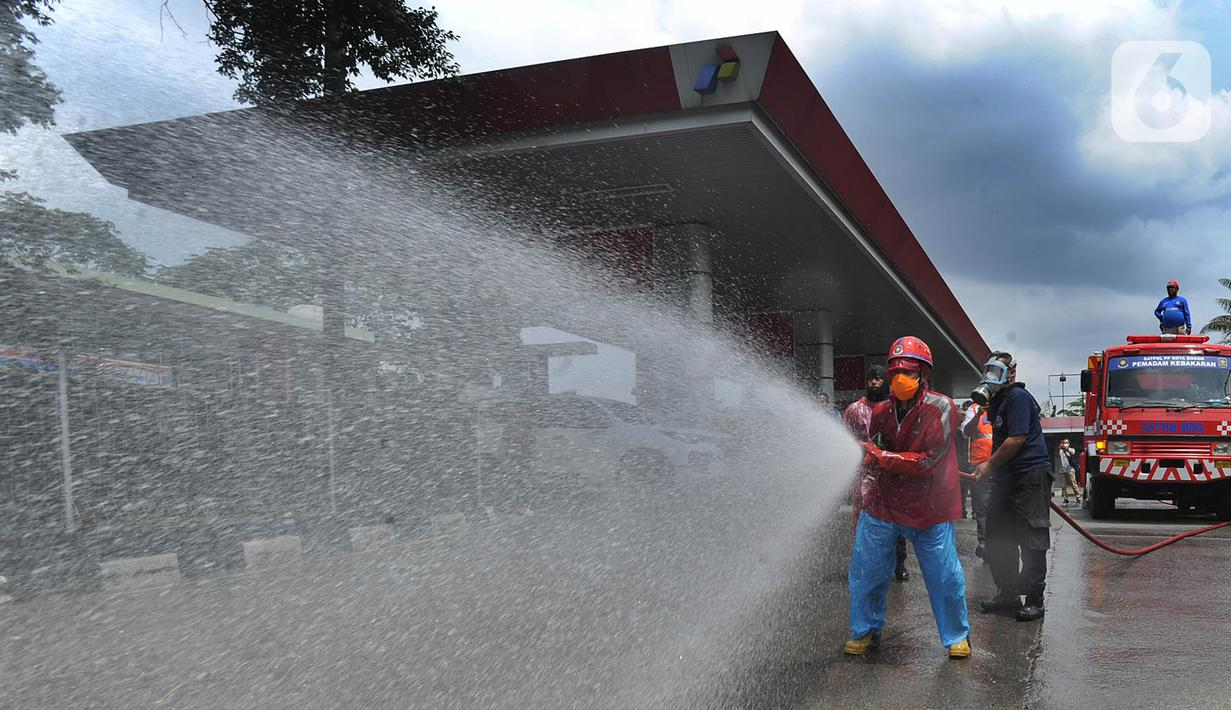 Petugas Pertamina dan Damkar melakukan penyemprotan disinfetaktan di SPBU depan RS Azra, Bogor, Jawa Barat, Jumat (27/03/2020). Hari ini seluruh SPBU di wilayah Bogor dilakukan penyemprotan disinfektan dalam rangka mencegah penyebaran wabah Covid-19. (merdeka.com/Arie Basuki)
