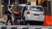 Seorang petugas memeriksa sebuah minubus yang digunakan dalam serangan di Mapolda Riau Rabu (16/5). (AP Photo/Akbari)
