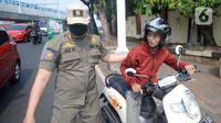 Petugas memberhentikan pengandara motor saat operasi yustisi protokol kesehatan untuk meningkatkan kesadaran dan kedisiplinan warga di Lebek Bulus, Jakarta, Senin (14/9/2020). Pemprov DKI memperketat kembali PSBB karena kasus Covid-19 mengalami peningkatan. (merdeka.com/Dwi Narwoko)