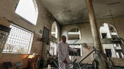 Seorang pria memeriksa kerusakan masjid yang terkena serangan udara Israel di Kota Gaza, Palestina (15/7). Serangan ini dilakukan untuk membalas Hamas yang melakukan peluncuran roket dan mortir ke wilayah selatan Israel. (AFP  Photo/Mahmud Hams)