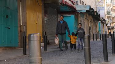 Warga berjalan saat lockdown di Kota Betlehem, Tepi Barat, Palestina, 19 Desember 2020. Lockdown dan jam malam penuh diberlakukan di Tepi Barat dan Jalur Gaza untuk mengendalikan meningkatnya jumlah infeksi dan kematian akibat COVID-19. (Xinhua/Mamoun Wazwaz)