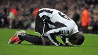 Mantan striker Newcastle United, Demba Ba, melakukan sujud syukur usai mencetak gol ke gawang Arsenal. (GLYN KIRK / AFP)