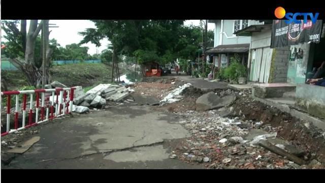 Kondisi jalan yang ambles mengakibatkan aktivitas warga di Jalan AL Mujahidin, Cipinang, pada Minggu pagi lumpuh.