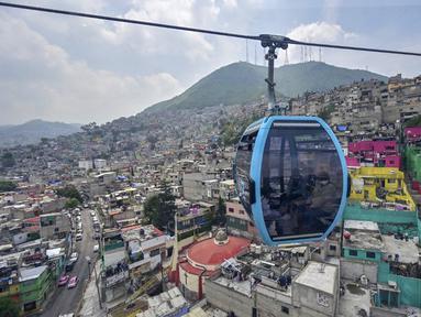 Penumpang melakukan perjalanan dengan sistem kereta gantung yang dijuluki Cablebus setelah peresmiannya di pinggiran Mexico City, Meksiko, 12 Juli 2021. Mexico City mulai mengoperasikan sistem kereta gantung yang menjanjikan untuk menghemat waktu bagi ribuan pengguna. (PEDRO PARDO/AFP)