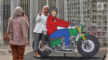 Pendukung calon Presiden no urut 01 Joko Widodo, menyempatkan foto bersama gambar karikatur Jokowi di Istora Senayan, Jakarta, Minggu (10/3). Mereka menghadiri Festival Satu Indonesia dengan penampilan topeng berwajah Jokowi. (Liputan6.com/Johan Tallo)