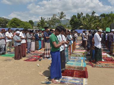 Umat muslim salat Jumat di sebuah ladang di dekat tempat penampungan sementara setelah gempa di Pemenang, Lombok (10/8). Menurut menteri senior, korban tewas akibat gempa dahsyat 6,9 SR di pulau Lombok melonjak di atas 300 orang. (AFP Photo/Adek Berry)