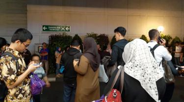 Sejumlah karyawan berkumpul di luar gedung perkantoran setelah merasakan gempa di Serpong, Tangerang pada Jumat (2/8/2019). Data dari BMKG, gempa dengan kekuatan magnitudo 7,4 mengguncang hingga Jakarta dan sekitarnya dengan pusat gempa berada di 147 km Barat Daya Sumur, Banten. (INDARYANI/AFP)