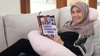 Hamil yang besar membuat Ratna membatasi aktivitasnya. Salah satu hal yang menjadi hiburan Ratna ialah membaca buku. Dengan tampil santai membaca buku, Ratna tetap terlihat begitu cantik memesona. (Liputan6.com/IG/@ratnagalih)