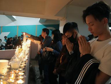 Para pengunjuk rasa berdoa di lokasi di mana mahasiswa Alex Chow Tsz-lok jatuh selama protes baru-baru ini di Hong Kong pada hari Jumat, (8/11/2019). Chow, seorang mahasiswa universitas Hong Kong  jatuh dari tempat parkir setelah polisi menembakkan gas air mata saat bentrokan. (AP Photo/Kin Cheung)