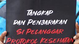 Seorang pengunjuk rasa membawa poster saat menggelar aksi di depan Gedung Polda Metro Jaya, Jakarta, Senin (7/12/2020). Massa menuntut aparat kepolisian segera menangkap Rizieq Shihab atas dugaan pelanggaran protokol kesehatan beberapa waktu lalu. (Liputan6.com/Immanuel Antonius)