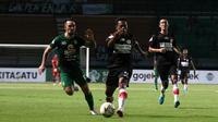 Gelandang Persebaya, Damian Lizio, berebut bola dengan pemain Persipura Jayapura, Yohanis Tjoe, dalam laga pekan ke-12 Shopee Liga 1 2019 di Stadion Gelora Bung Tomo, Surabaya, Jumat (2/8/2019). (Bola.com/Aditya Wany)