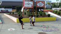 Pengunjung berada di dekat tembok mural di area RTH/RPTRA Kalijodo, Jakarta. Selasa (24/7). Sebelumnya, warganet ramai membahas di media sosial ihwal kondisi RTH dan RPTRA Kalijodo yang terlihat terbengkalai. (Liputan6.com/Helmi Fithriansyah)