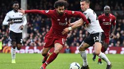 Aksi Mohamed Salah lewati gelandang Fulham, Joe Bryan pada laga lanjutan Premier League yang berlangsung di Stadion Craven Cottage, London, Minggu (17/3). Liverpool menang 2-1 atas Fulham. (AFP/Glyn Kirk)