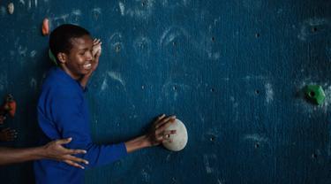 Seorang remaja tuna netra bernama Dominic Hezron mencoba menyentuh papan panjat dinding saat acara pelatihan di Nairobi, Kenya (15/3). Latihan panjat dinding tuna netra ini diselenggarakan oleh NPO Monkey Magic. (AFP/Yasuyoshi Chiba)