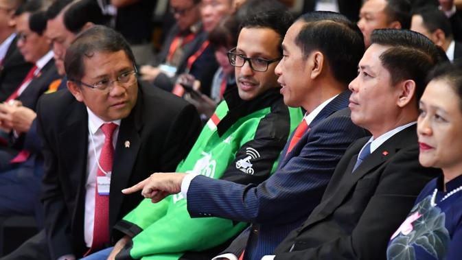 Presiden Jokowi berbincang dengan CEO Go-Jek, Nadiem Makarim saat peluncuran aplikasi Go-Viet di Hanoi, Rabu (12/9). Goviet merupakan produk aplikasi penyedia jasa transportasi di Vietnam yang berkolaborasi dengan Goje. (Liputan6.com/HO/Biro Pers Setpres)
