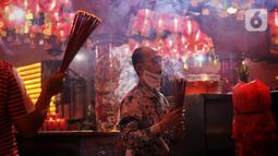 Warga keturunan Tionghoa melakukan sembahyang malam Imlek di Klenteng Boen San Bio, Tangerang, Kamis (11/2/2021). Meskipun di tengah pandemi Covid 19, sembahyang Imlek 2572 dilakukan dengan protokol kesehatan yang cukup ketat dan membatasi jumlah warga yang sembahyang. (Liputan6.com/Angga Yuniar)