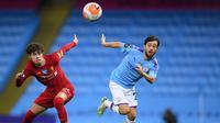 Gelandang Liverpool, Neco Williams berebut bola dengan gelandang Manchester City, Bernardo Silva  pada pertandingan lanjutan Liga Inggris  di Stadion Etihad di Manchester, Inggris (2//7/2020). City menang telak 4-0 atas Liverpool. (AFP/Pool/Laurence Griffiths)