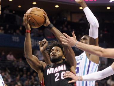 Pemain Miami Heat, Justise Winslow #20 berusaha melewati hadangan para pemain Charlotte Hornets pada laga NBA di Spectrum Center, (29/12/2016). Hornets menang 91-82. (Reuters/Sam Sharpe-USA TODAY Sports)
