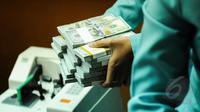Aktivitas penukaran uang di PT Ayu Masagung, Jakarta, Senin (9/3/2015). Pada awal perdagangan di pasar spot, rupiah dibuka pada level 12.994 atau melemah 18 poin dibanding penutupan akhir pekan lalu di posisi 12.976. (Liputan6.com/Faizal Fanani)