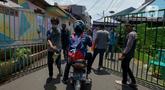 Anggota Karang Taruna menyemprotkan cairan disinfektan ke kendaraan yang memasuki pemukiman di Kelurahan Kebon Sirih, Jakarta, Rabu (1/4/2020). Warga di kelurahan itu memberlakukan akses satu pintu masuk dan menyemprotkan disinfektan guna mencegah penyebaran virus COVID-19. (merdeka.com/Imam Buhori)