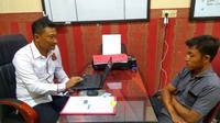 Dodik Iswahyudi, warga Desa Pongpongan, Kecamatan Merakurak, Kabupaten Tuban, saat diperiksa angggota Satreskrim Polres Tuban. (Yudi Handoyo/JawaPos.com)