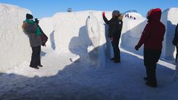 Orang-orang bermain di labirin salju yang dibuat oleh pasangan suami istri, Clint dan Angie Masse di St. Adolphe, Kanada, 3 Maret 2019. Labirin seluas 2.789 meter per segi ini telah memecahkan rekor sebagai yang terbesar di dunia. (Thibault JOURDAN/AFP)