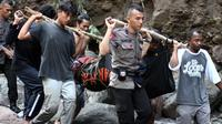 Petugas kepolisian dan warga saat mengevakuasi salah satu jenazah korban banjir bandang di kawasan Air Terjun Dua Warna, Sibolangit, Deli Serdang, Sumatera Utara, Senin (16/5). 17 jenazah korban dilaporkan telah ditemukan. (ALBERT DAMANIK / AFP)