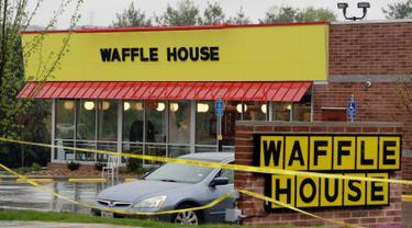 Garis polisi terpasang di lokasi penembakan yang terjadi di  area restoran Waffle House dekat Nashville, Tennessee, Minggu (23/4). Seorang pria telanjang hanya berjaket hijau menembak mati sedikitnya empat orang di kedai tersebut. (AP Photo/Mark Humphrey)