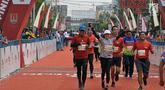 Pelari tiba di garis finish saat mengikuti Semarang 10K di Kota Semarang, Jawa Tengah, Minggu (16/12). Sebanyak 2.000 pelari mengikuti Semarang 10K. (Liputan6.com/Gholib)